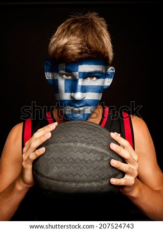 portrait of basketball player with greek flag painted on his face - stock photo