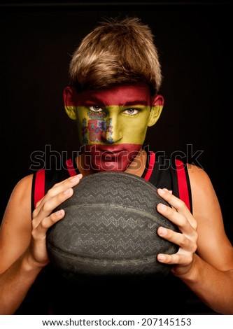 portrait of basketball player with spanish flag painted on his face - stock photo