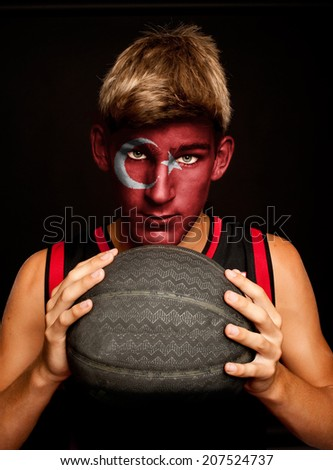 portrait of basketball player with turkish flag painted on his face - stock photo