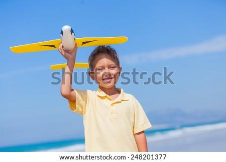 Portrait of beach kid boy kite flying outdoor coast ocean - stock photo