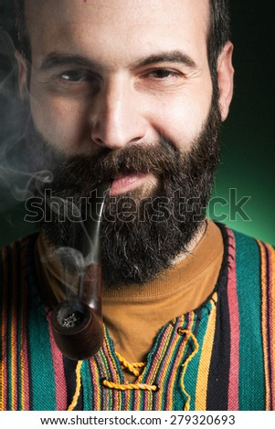 Portrait of beard man smoking tobacco pipe. Pipe is smoke/Beard man smoking tobacco pipe - stock photo