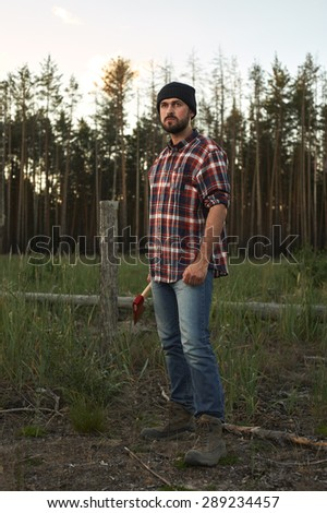 Portrait of bearded Lumberjack with Hat, Boots, Shirt and Ax in a Forest - stock photo
