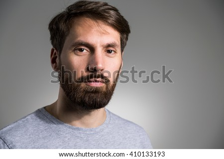 Portrait of bearded man in grey shirt looking at the camera on light grey background - stock photo