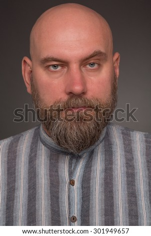 Portrait of bearded man in prison garb. Bold serious man in lined shirt posing on dark grey. - stock photo