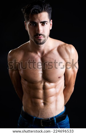 Portrait of beautiful and muscular man in dark background.  - stock photo