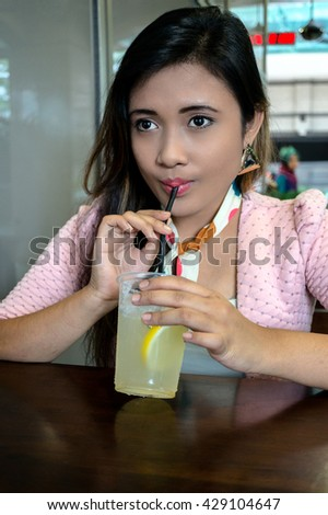 Portrait of beautiful asian college girl student sitting on campus cafe, drink lemon ice, feel relax and enjoy - stock photo