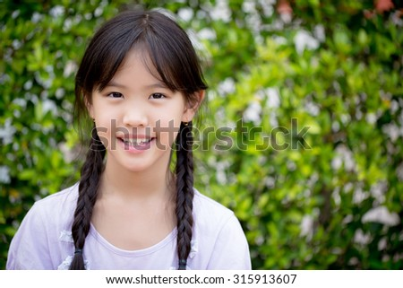 Portrait of beautiful Asian girl smiling in the garden - stock photo