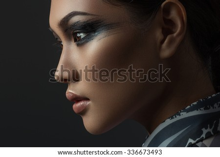 Portrait of beautiful asian girl with creative art make up. Picture taken in the studio on a black background. - stock photo