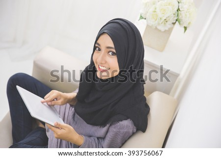 Portrait of beautiful asian girl with tablet computer at home - stock photo