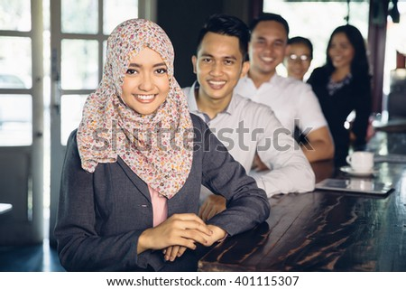 portrait of beautiful asian muslim businesswoman wearing scarf standing in front of her team - stock photo