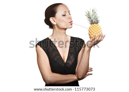 Portrait of beautiful Asian woman drinking juice through pineapple in studio isolated on white background - stock photo