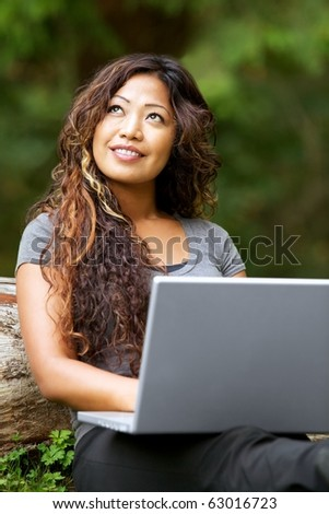 Portrait of beautiful Asian woman using laptop outdoor - stock photo