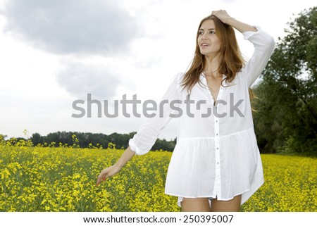 Portrait of beautiful attractive and sensuality sexy pretty brunette woman in white shirt on a yellow flowers field and blue sky - stock photo