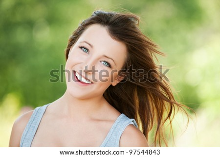 Portrait of beautiful attractive young smiling woman at summer green park - stock photo