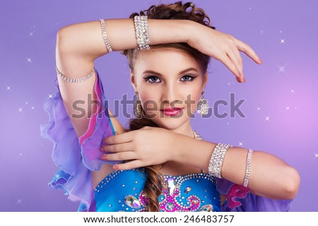 Portrait of beautiful belly dancer girl with nice makeup and heardress is wearing a colorful fashion costume. Isolated on purple - stock photo
