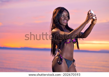 Portrait of beautiful black African American woman posing to take a selfie with her smartphone on the beach at sunset - stock photo