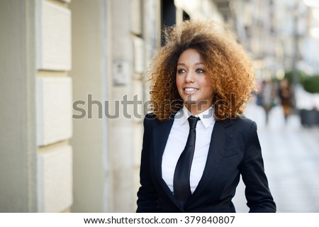 Portrait of beautiful black businesswoman wearing suit and tie smiling in urban background. Woman with afro hairstyle. - stock photo