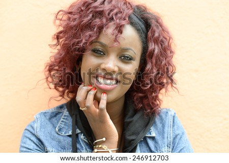Portrait of beautiful black woman in urban background smiling. White teeth - stock photo