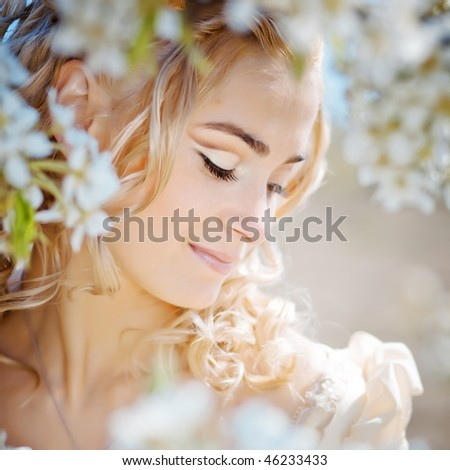 Portrait of beautiful blond bride in spring blossom - stock photo