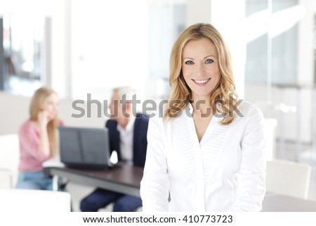Portrait of beautiful blond businesswoman standing at office while her colleagues working at background.  - stock photo