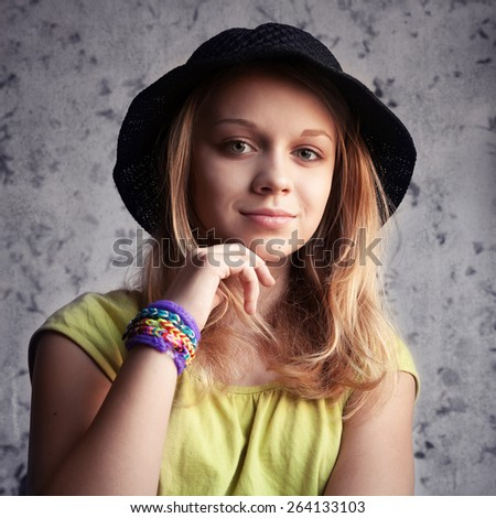 Portrait of beautiful blond teenage girl in black hat and rubber loom bracelets. Vintage toned photo filter, instagram style effect - stock photo