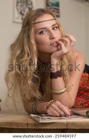 portrait of beautiful blond woman dressed as hippie reading magazine - stock photo