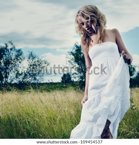 Portrait of beautiful blond woman in a field - stock photo