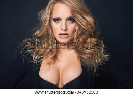 Portrait of beautiful blond woman in black jacket and bra - stock photo