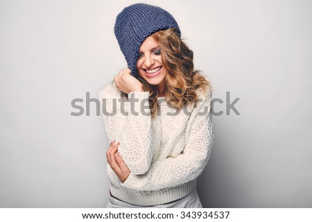 Portrait of beautiful blond woman in white in white sweater and blue hat - stock photo