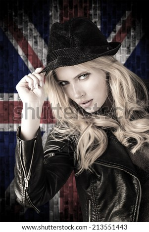 Portrait of beautiful blond woman over a British flag. - stock photo