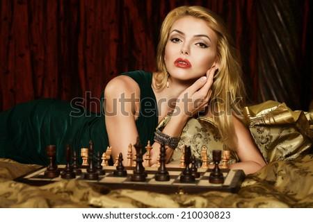 Portrait of beautiful blond woman playing chess - stock photo