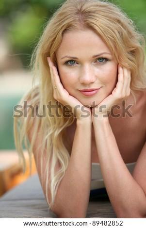 Portrait of beautiful blond woman relaxing in garden - stock photo