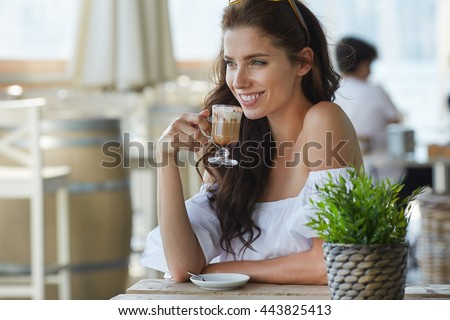Portrait of beautiful blond woman sitting in outdoors cafe in Italy, drinking coffee - stock photo