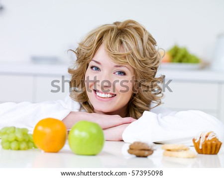 Portrait of beautiful blond woman with fruits and cakes sitting on the kitchen - stock photo