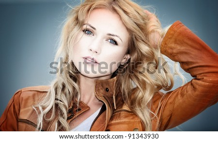 Portrait of beautiful blond woman with leather jacket - stock photo