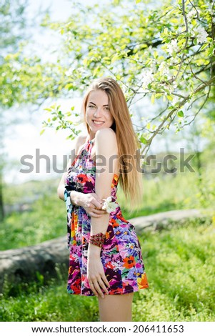 portrait of beautiful blond young woman having fun posing with great smile & looking at camera on green summer copy space outdoors background - stock photo