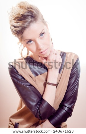 portrait of beautiful blond young woman with collected hair & blue eyes in brown leather dress looking at camera on white copyspace - stock photo