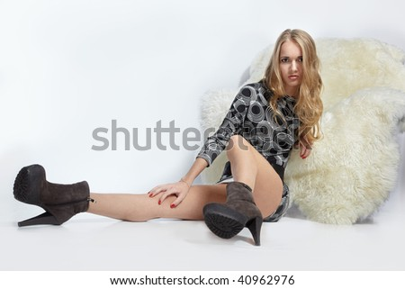 portrait of beautiful blonde blue-eyed girl sitting near furry arm-chair - stock photo
