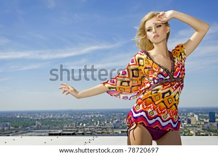portrait of beautiful blonde girl in colored blouse on background blue sky - stock photo