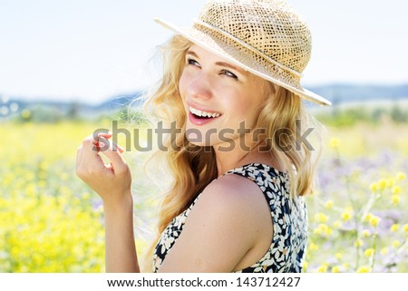 Portrait of beautiful blonde girl in the field of flowers - stock photo