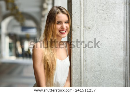 Portrait of beautiful blonde girl in urban background wearing white dress in urban background - stock photo