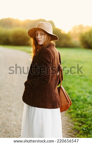 Portrait of beautiful blonde girl walking down the countryside road in sunset light. Outside - stock photo
