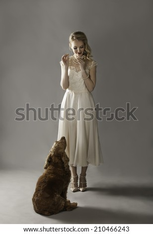 Portrait of beautiful blonde lady feeding her cute spaniel dog treats while it waits patiently - stock photo
