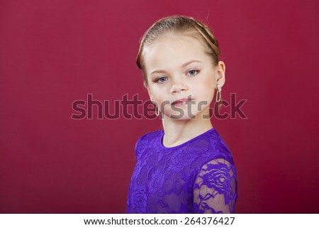 Portrait of beautiful blonde little girl, studio on dark red background  - stock photo