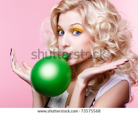 portrait of beautiful blonde party girl blowing up green balloon - stock photo