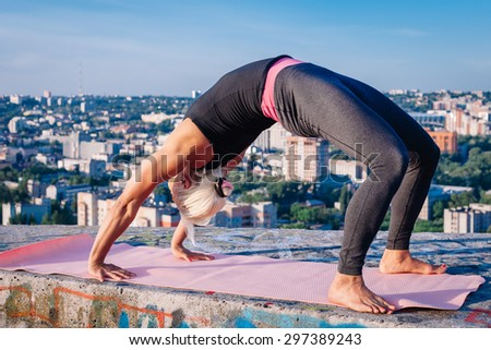 Portrait of beautiful blonde strong woman in sportwear doing workout yoga exercise and stretching on the roof of a skyscraper above the big city. Female sporty muscular body. Sunrise sunny light. - stock photo