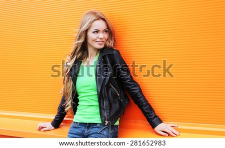 Portrait of beautiful blonde woman wearing a black rock leather jacket against the colorful orange wall, street fashion - stock photo