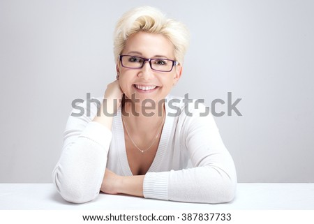 Portrait of beautiful blonde woman with short hairstyle. Woman in eyeglasses. Looking at camera, smiling. Studio shot. - stock photo