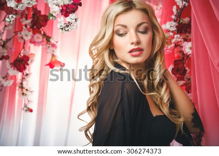 Portrait of beautiful blonde young woman in black lingerie over flowers background - stock photo