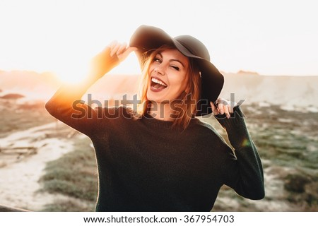 Portrait of beautiful blonde young woman in glasses and holding hat and winking on the beach with sunset light.  - stock photo